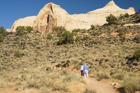 Visitors hike along the trail to Hickman Bridge in Capital Reef National Park in southern Utah.  Capital Dome formation in the background. Reklamní fotografie