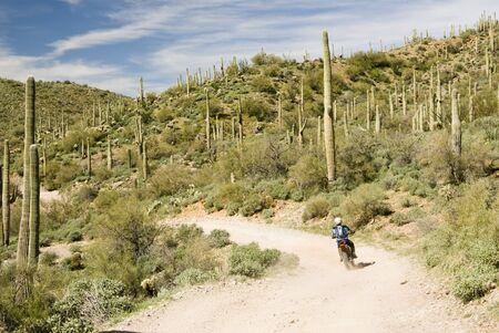a dirt biker traveling through the Sonoran desert wilderness in Arizona photo