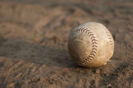 dirty: Softball laying in dirt.