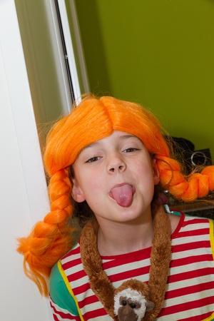 Klein meisje in kostuum steekt tong uit Stockfoto