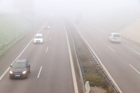 hydroplaning: Bad Weather Driving - car driving on a freeway on a rainy and misty day