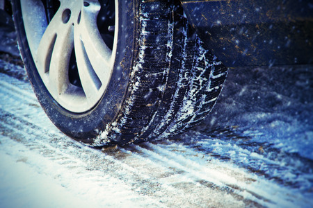 traction: Winter tire in snow closeup Stock Photo