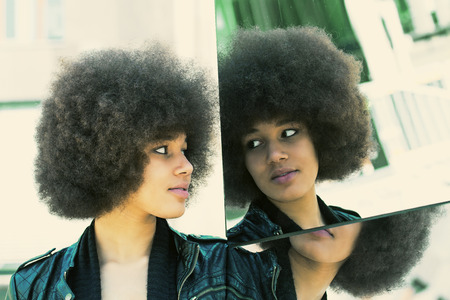 afro girl: Modern afro girl looking in a mirror Stock Photo