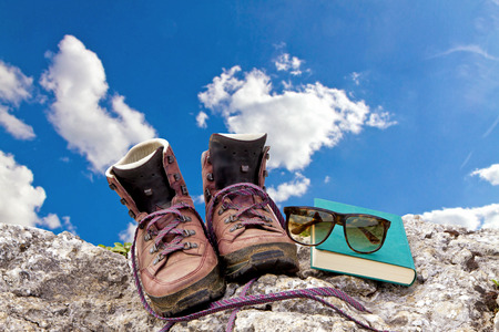 glass break: Hiking boots, book and sunglasses Stock Photo