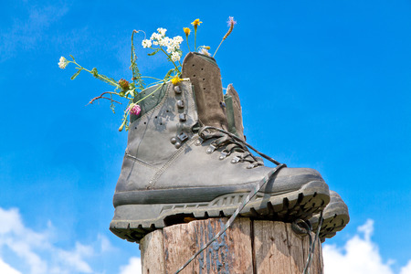 Hiking boots with flowers on a wooden stake
