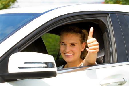 Happy girl in a car with thumb up photo