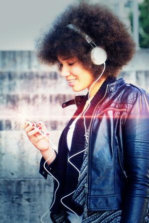 Muchacha con los auriculares en la ciudad - foto con efecto de luz Foto de archivo - 34704192