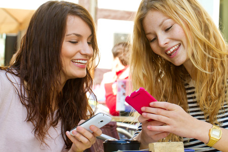 two people only: Girls with smartphones in a cafe