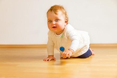 bebe gateando: Bebé en un piso de madera Foto de archivo