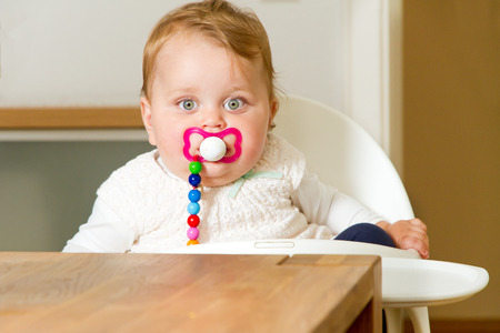 highchair: Cute baby sitting on a high chair Stock Photo