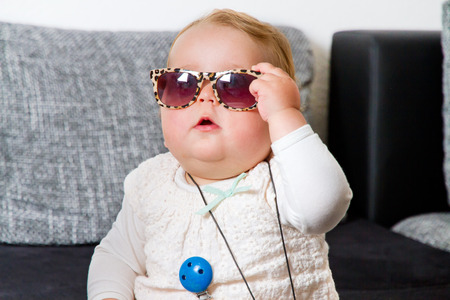 Funny baby with sunglasses at home