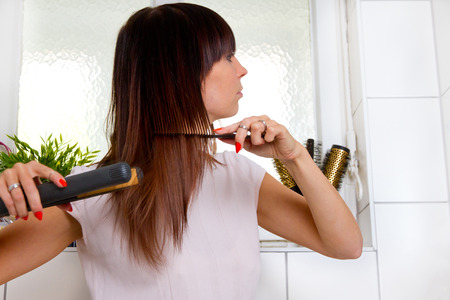 straightener: Young woman in bathroom with hair straightener Stock Photo