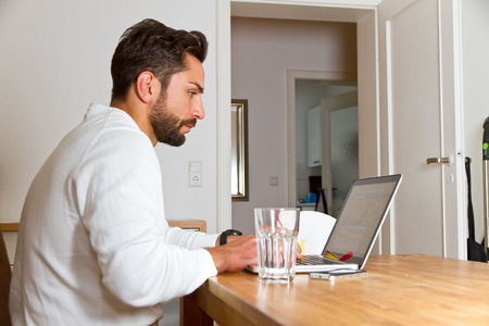 A young caucasian man working in his home office Standard-Bild