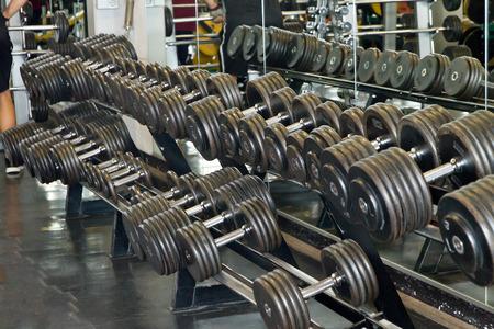 dumb bells: Dumb bells lined up in a fitness studio Stock Photo