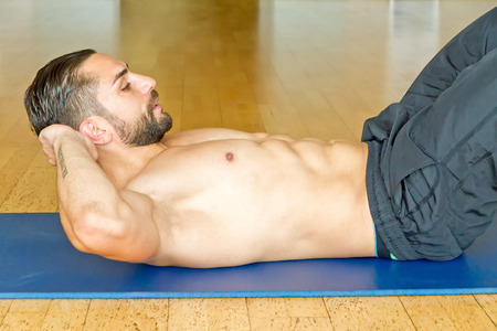 sit ups: Muscular man doing abdominal crunches in gym