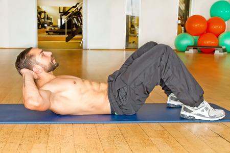 Muscular man doing abdominal crunches in gym photo