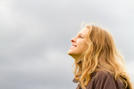 Happy young woman looking in to the sky Standard-Bild