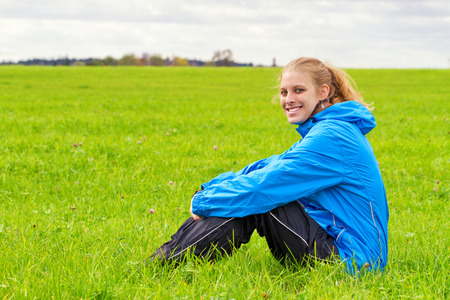 Sporty woman sitting on a meadow photo