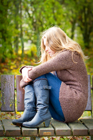 abused women: Depressive woman sitting on a park bench Stock Photo