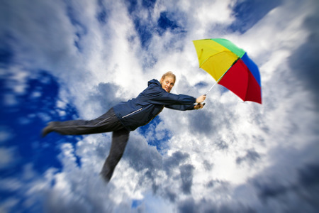 Woman flying in the clouds with umbrella photo