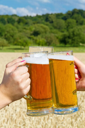 Hands with beer mugs photo