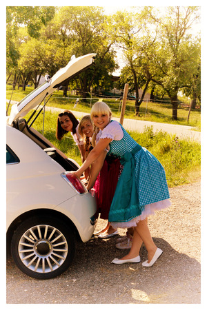 three girls: Three girls in dirndls on her new car