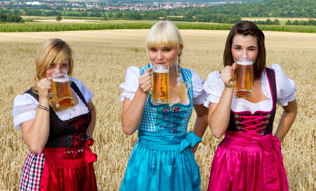 three girls: Three girls in dirndl drinking beer Stock Photo