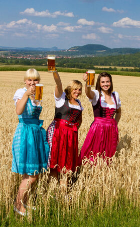 three girls: Three girls in dirndl with beer mugs Stock Photo