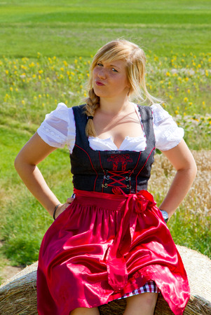 cheeky: Cheeky Ggirl in a dirndl sitting on a straw ball Stock Photo