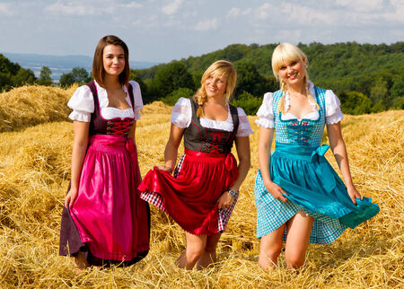 dirndl dress: Three happy girls in dirndl having fun on a field Stock Photo