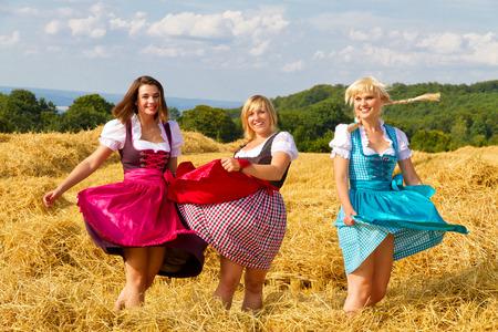 Tres chicas en el baile dirndl en un campo Foto de archivo - 34947269