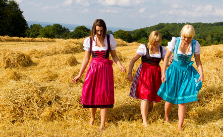 three girls: Three girls in dirndl walking on a straw field