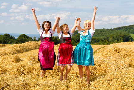 three girls: Three girls in dirndl having fun on a field