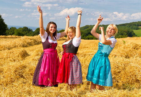 three girls: Three girls in dirndl dancing on a field