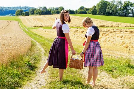 Sleeptouw meisjes in dirndl lopen met een picknickmand