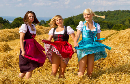 dirndl: Three girls in dirndl dancing on a field