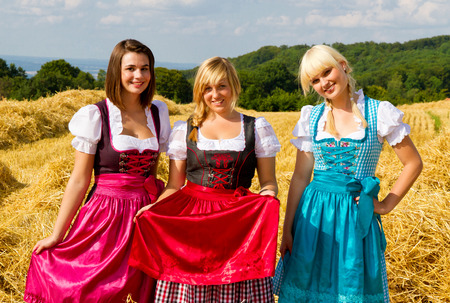 Three girls in colorful dirndl Фото со стока