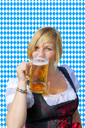 Girl in a dirndl drinking beer, in background bavarian pattern photo