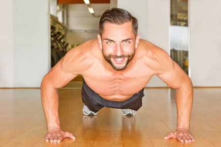 Athletic, happy man making push ups photo