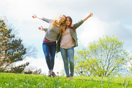 Two dancing girls on a meadow