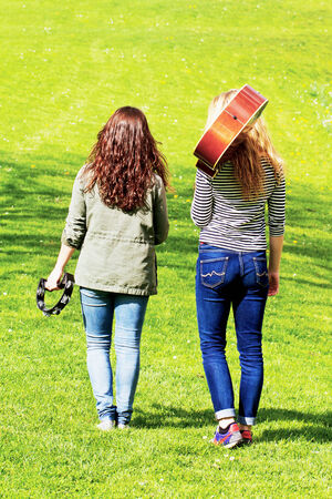 Two girls walking in a park with music instruments photo