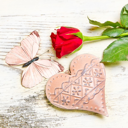 rose butterfly: Red rose, butterfly and heart on white wooden background