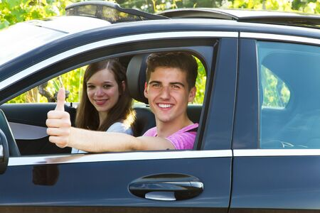 two thumbs up: Young couple with thumb up in their new car