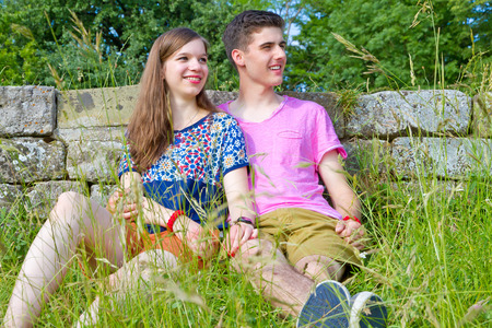 nearness: Young happy couple sitting in a meadow