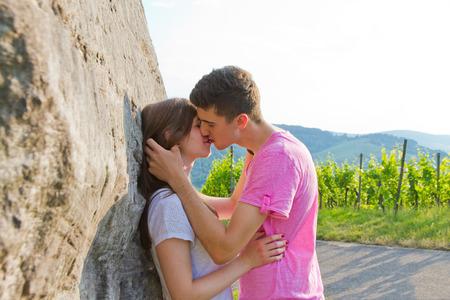 personas abrazadas: Joven pareja besándose en la naturaleza