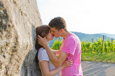 two girls hugging: Young couple kissing in nature