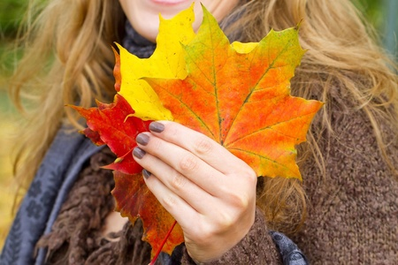 color: Woman with colorful autumn leaves in the hand