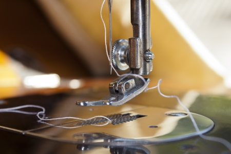 threading: Closeup of a sewing machine threading  Foot, needle and thread