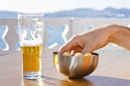 near beer: A hand picking snacks from a bowl and a beer in a table of a terrace near the sea in a sunny summer day
