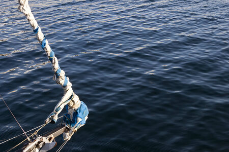 furled: Furled staysail jib in the bowsprit of the bow of a yacht in the sea  Stock Photo